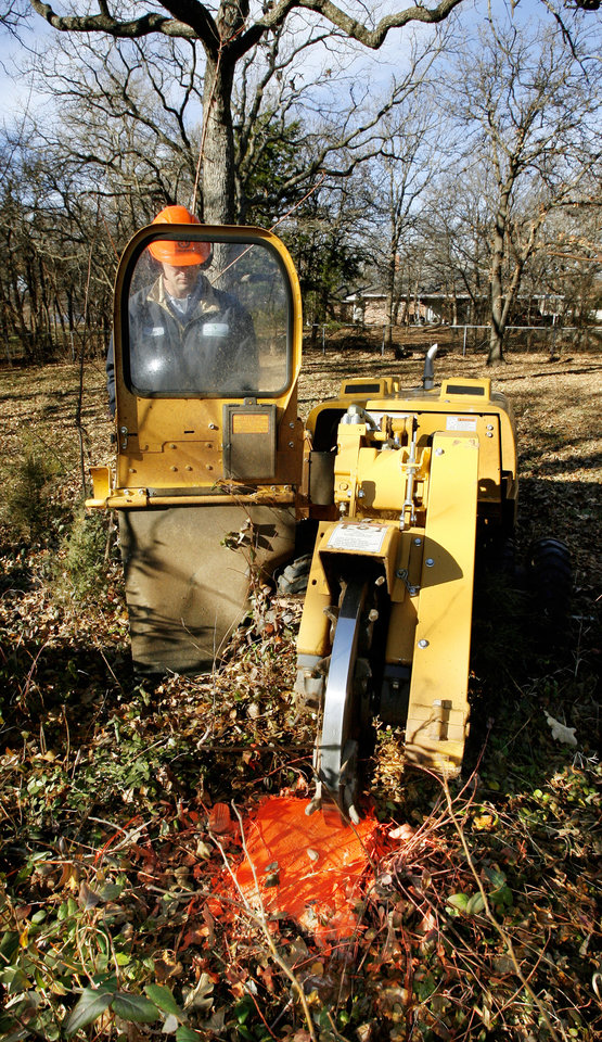 Photo - Samuel White with Horticultural Solutions Inc., using a stump grinder to remove a stump in the Arrowhead Hills housing addition in Edmond Wednesday, Jan. 9, 2008. BY PAUL B. SOUTHERLAND, THE OKLAHOMAN ORG XMIT: KOD