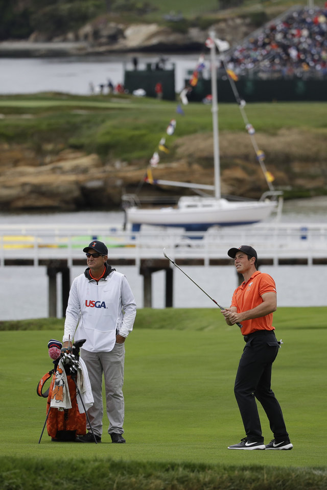Photo - Oklahoma State's Viktor Hovland hits from the fairway on the fourth hole during the final round of the U.S. Open Championship at Pebble Beach Golf Links as his caddie, OSU coach Alan Bratton, watches. [AP PHOTO]