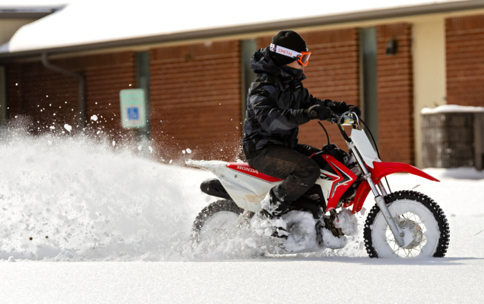 Photo - A person rides a motorcycle through the snow in Oklahoma City, Okla. on Wednesday, Feb. 17, 2021.  [Chris Landsberger/The Oklahoman]