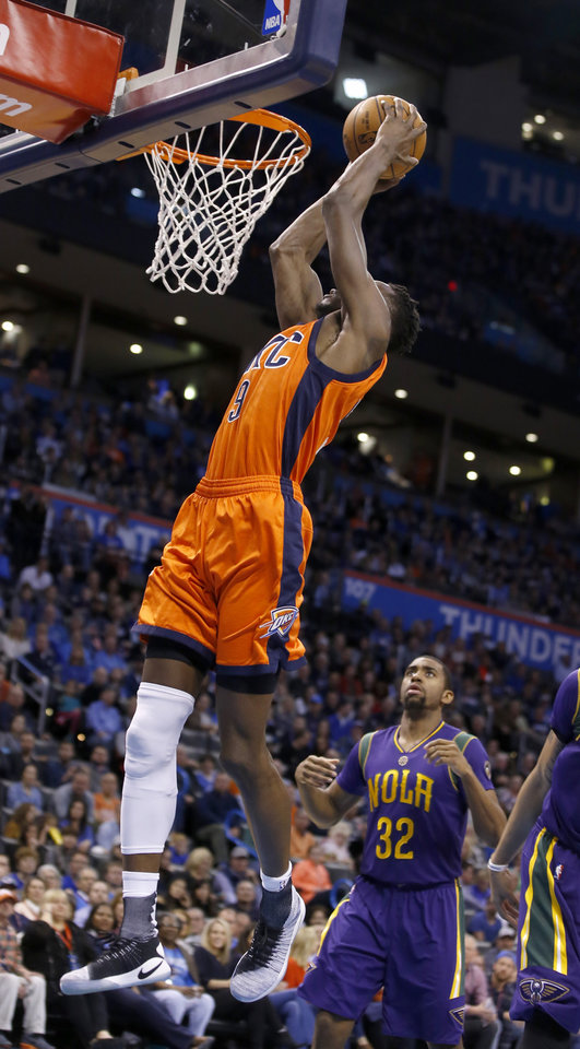 Photo - Oklahoma City's Jerami Grant (9) goes up for a dunk as New Orleans' Hollis Thompson (32) looks on during the NBA basketball game between the Oklahoma City Thunder and the New Orleans Pelicans at the Chesapeake Energy Arena, Saturday, Feb. 25, 2017.  Photo by Sarah Phipps, The Oklahoman