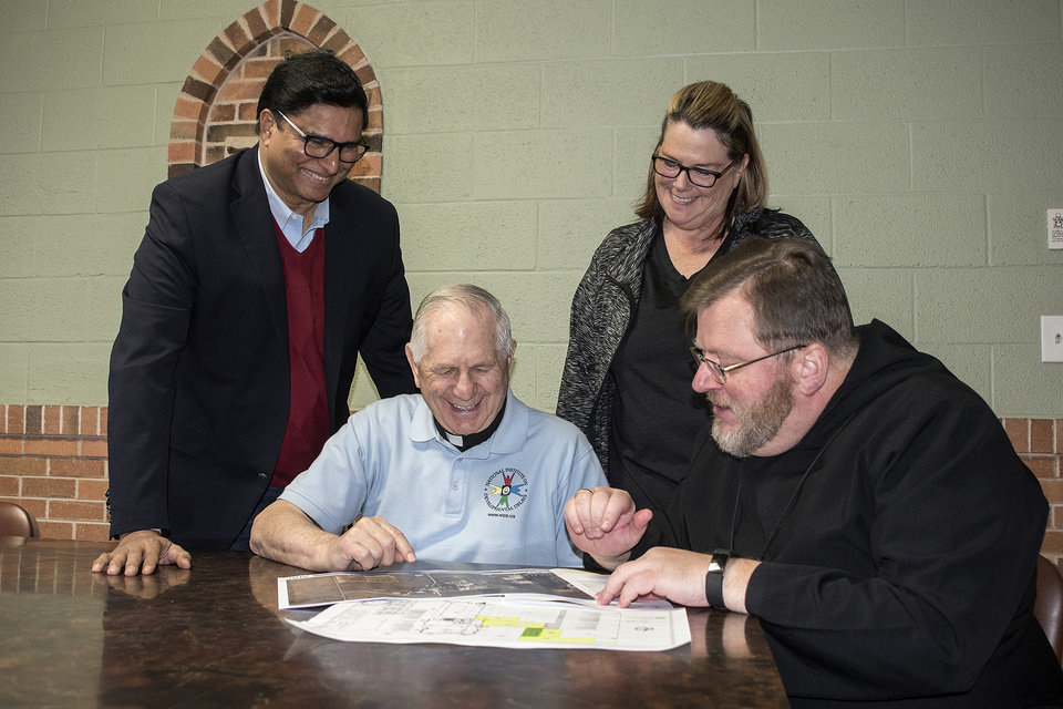 Photo -  Leaders with the National Institute on Developmental Delays/Home Integration Inc., Mohan Chandran, the Rev. Paul Zahler, O.S.B., and Virginia Reeves meet with Abbot Lawrence Stasyszen, O.S.B., to look at plans to build the nonprofit's new facilities on abbey land. [Photo by Theresa Bragg]
