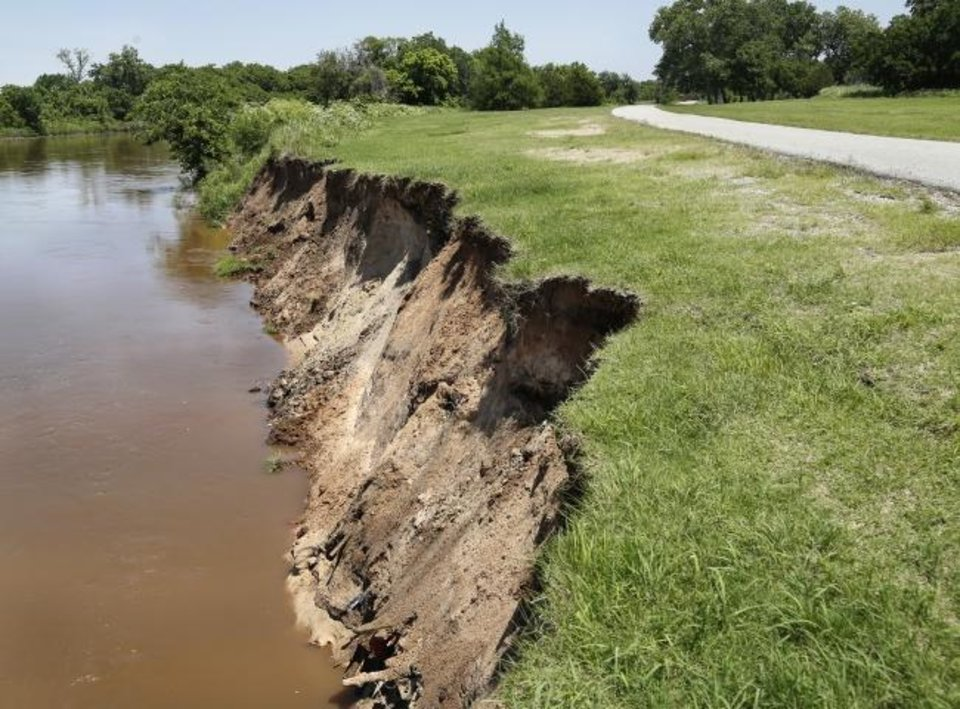 Photo -  Erosion on the south bank of the North Canadian River along the West River Trail shown in this photo taken Thursday briefly closed some sections of the trail. The trail was reopened Friday after workers shored up some of the flooding damage.  [JIM BECKEL/THE OKLAHOMAN]