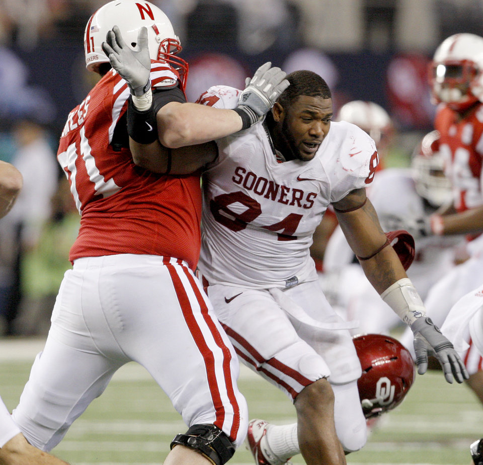 Photo - OU's Pryce Macon has his helmet knocked off by Nebraska's Jeremiah Sirles during the Big 12 football championship game between the University of Oklahoma Sooners (OU) and the University of Nebraska Cornhuskers (NU) at Cowboys Stadium on Saturday, Dec. 4, 2010, in Arlington, Texas.  Photo by Bryan Terry, The Oklahoman