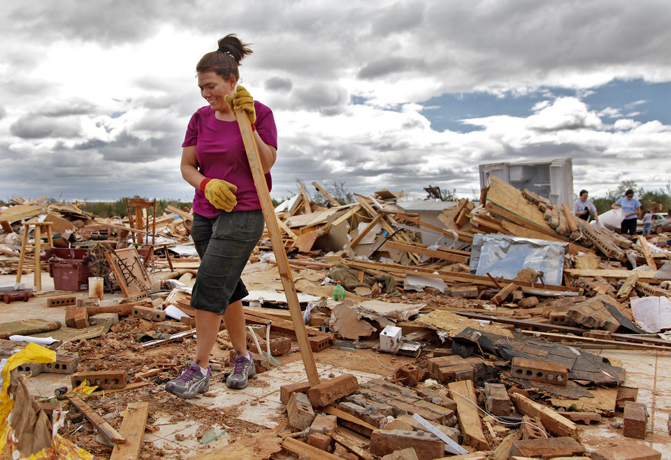 Photo - Miranda Lewis smiles as she recovers the height growth marker for her six-year-old son Copper among the rubble left behind after the home was destroyed by Tuesday's tornado west of El Reno, Wednesday, May 25, 2011. Photo by Chris Landsberger, The Oklahoman