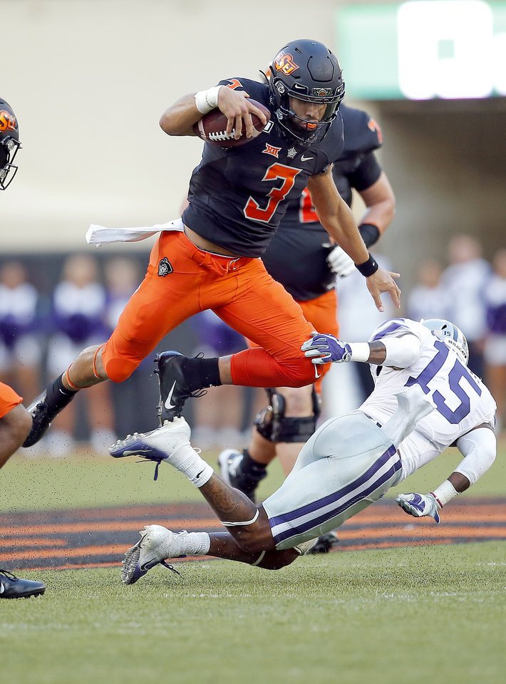 Photo - Oklahoma State's Spencer Sanders (3) leaps over Kansas State's Walter Neil Jr. (15) in the first quarter during the college football game between the Oklahoma State Cowboys and the Kansas State Wildcats at Boone Pickens Stadium in Stillwater, Okla., Friday, Sept. 27, 2019. [Sarah Phipps/The Oklahoman]