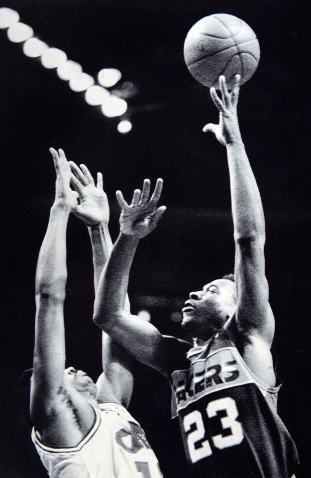 Photo - Former OU basketball player Wayman Tisdale. RICHFIELD, Ohio, Dec. 20--CAPTAIN HOOK--Indiana Pacers Wayman Tisdale (23) lofts a hook shot over Cleveland Cavalier defender John Williams in the 1st quarter of Sunday's game in the Richfield Coliseum. (AP Laserphoto) 1987. Photo taken 12/20/1984, Photo published 12/21/1984 in The Daily Oklahoman. ORG XMIT: KOD