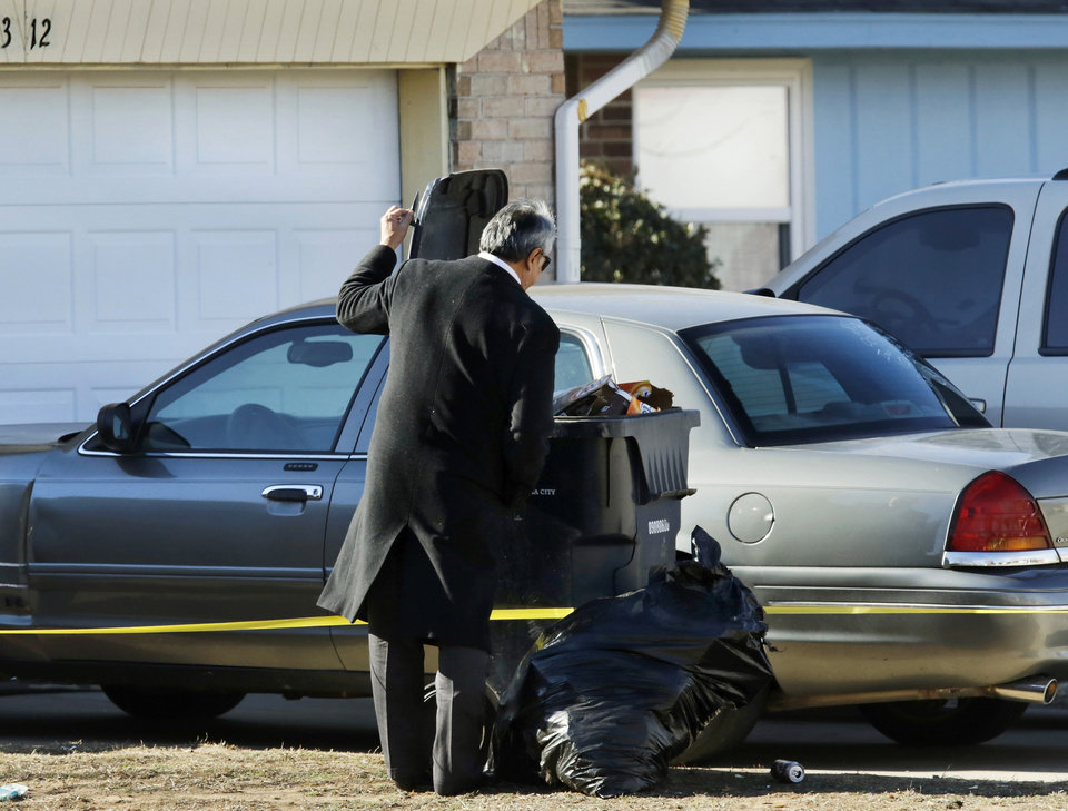 Photo - A detective opens the lid of a trash receptacle in front of the house. Oklahoma City police crime scene investigators and detectives are shown at crime scene at a home near NE 23 and Bryant, 3300 block of NE 19, on Wednesday, Jan. 4, 2017. It is believed there is one adult male dead inside the residence. Photo by Jim Beckel, The Oklahoman]