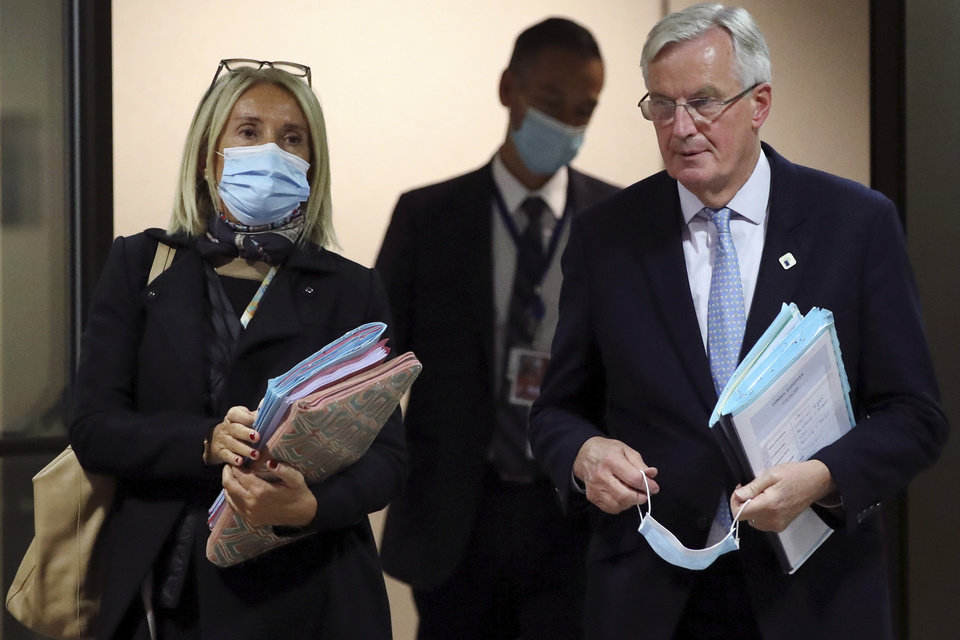 Photo -  European Commission's Head of Task Force for Relations with the United Kingdom Michel Barnier, right, leaves after addressing a media conference at an EU summit in Brussels, Thursday, Oct. 15, 2020. European Union leaders met in person for the first day of a two-day summit, amid the worsening coronavirus pandemic, to discuss topics ranging from Brexit to climate and relations with Africa. (Yves Herman, Pool via AP)