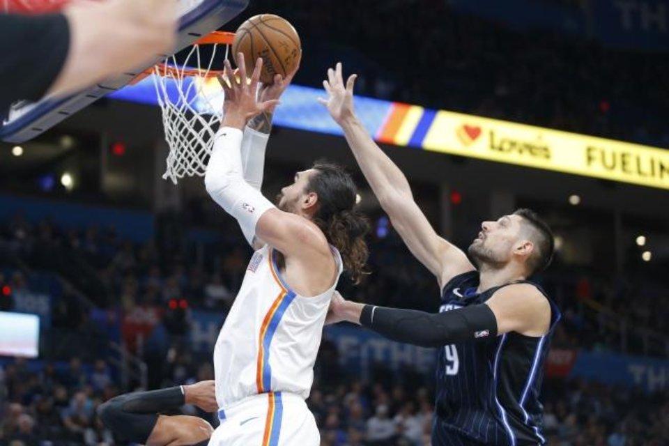 Photo -  Oklahoma City center Steven Adams, left, puts up a shot beside Orlando's Nikola Vucevic during Tuesday night's NBA game at Chesapeake Energy Arena. [Bryan Terry/The Oklahoman]