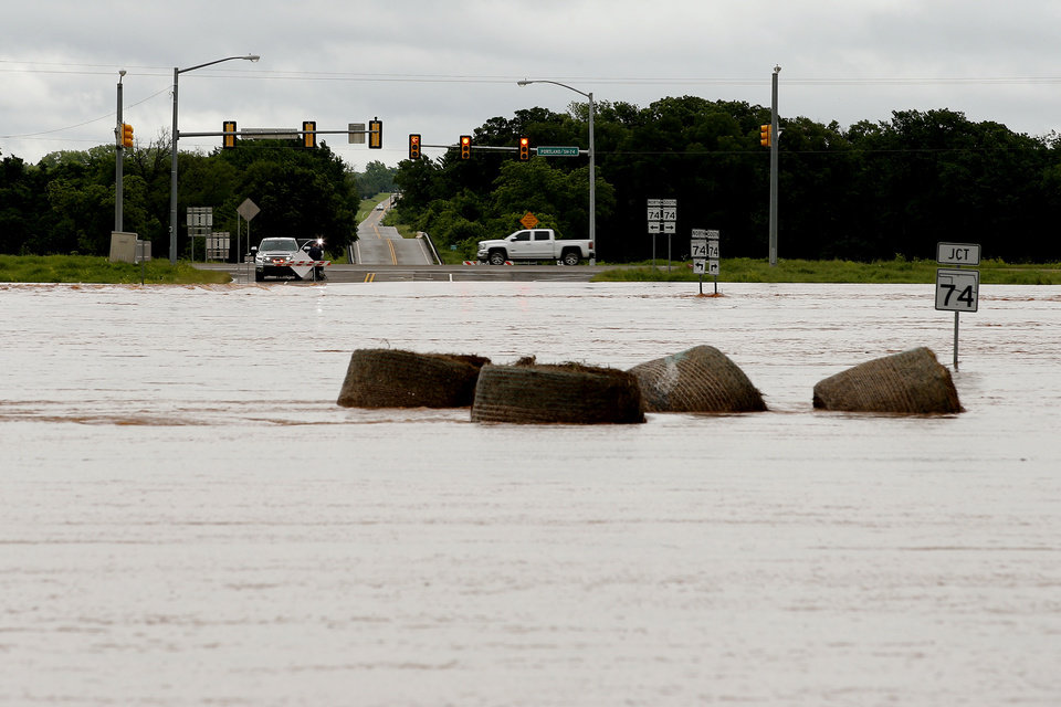 Photo - Floodwaters carry hay bales over over NW 178 just west of portland in Oklahoma City, Tuesday, May 21, 2019. [Bryan Terry/The Oklahoman]