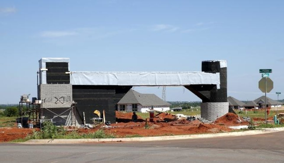 Photo -  An entrance at a new housing development is pictured in northwest Oklahoma City near the twin silos of what was once the Genzer farm.