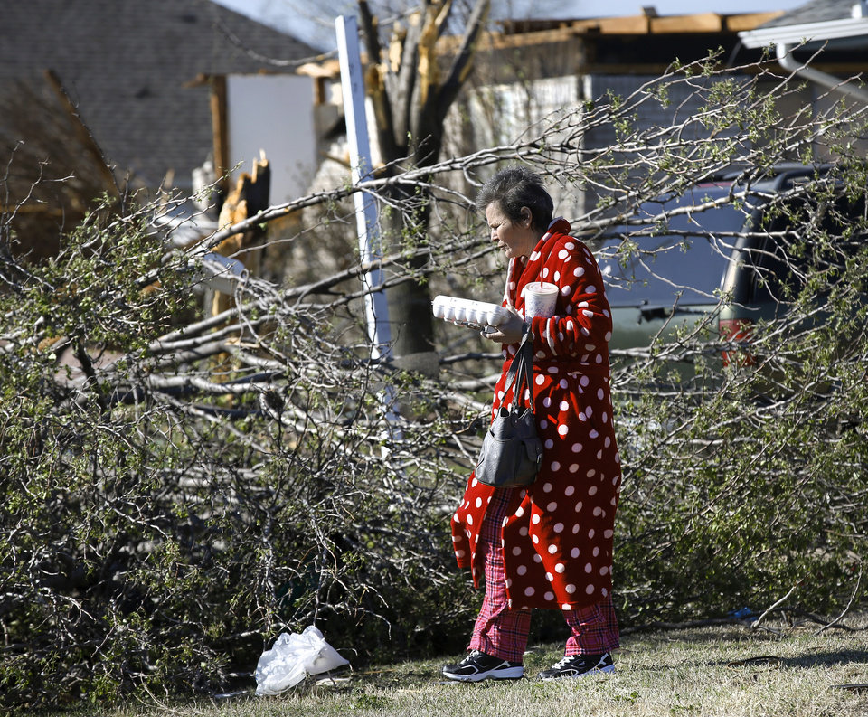 Photo - A woman carries eggs to a car  as she is driven to a relative's home where there is electricity. Neighborhood  between NW 5 and Main Street, and between Telephone Rd. and Santa Fe in Moore.  Thursday morning, March 26, 2015, the day after a tornado damaged homes and a school Wednesday evening. Photo by Jim Beckel, The Oklahoman