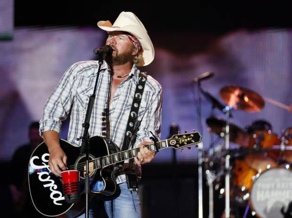 Photo - Toby Keith performs at the end of the Oklahoma Twister Relief Concert, benefiting victims of the May tornadoes, at Gaylord Family - Oklahoma Memorial Stadium on the campus of the University of Oklahoma in Norman, Okla., Saturday, July 6, 2013. Photo by Nate Billings, The Oklahoman Archives