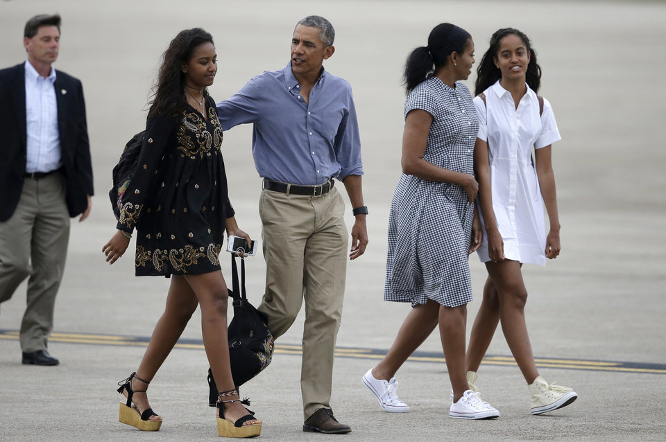Photo - President Barack Obama, center, and first lady Michelle Obama, second from right, walk with their daughters, Sasha, left, and Malia on the tarmac to board Air Force One at the Cape Cod Coast Guard Station, in Bourne, Mass., Sunday, Aug. 21, 2016. President Obama and the first family are returning to Washington D.C. following their vacation on the island of Martha's Vineyard, in Massachusetts. (AP Photo/Steven Senne)