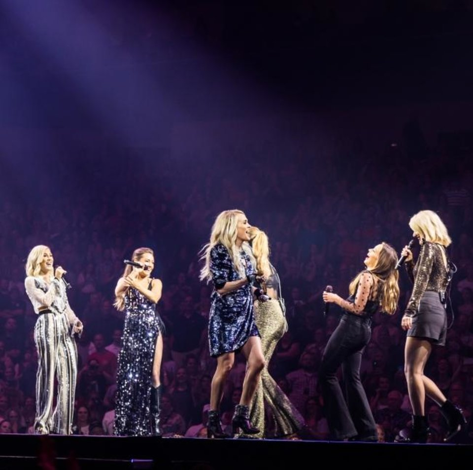 Photo -  Carrie Underwood, center, performs in concert with the members of Runaway June, left, and Maddie & Tae, right. [Amanda Young]