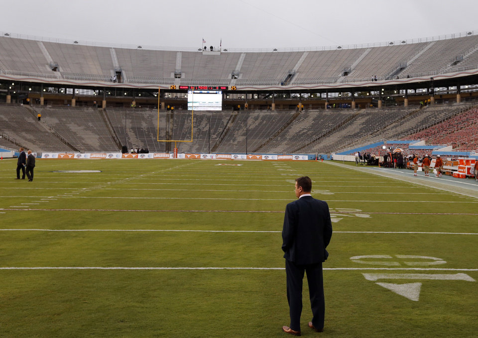 Photo - Head coach Bob Stoops examines the field before the Red River Showdown college football game between the University of Oklahoma Sooners (OU) and the University of Texas Longhorns (UT) at the Cottonbowl in Dallas, Texas on Saturday, Oct. 11, 2014. 