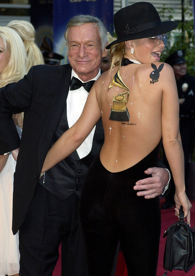Photo - ** ADVANCE FOR WEEKEND EDITIONS, JUNE 12-15--FILE **Playboy Magazine publisher Hugh Hefner, who founded the Playboy Jazz Festival in 1979, arrives at the 44th annual Grammy Awards with Playboy playmate Zoe Gregory in this Feb. 27, 2002, file photo in Los Angeles. Hefner is celebrating the 25th anniversary of the jazz festival, a two-day summertime celebration featuring a range of musical styles.  (AP Photo/Mark J. Terrill)