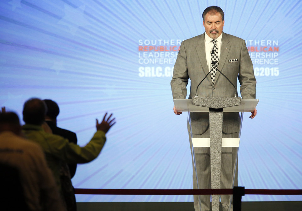 Photo - Paul Blair leads the invocation at the start of the final day of the Southern Republican Leadership Conference at the Cox Convention Center in Oklahoma City, Saturday, May 23, 2015. Photo by Nate Billings, The Oklahoman