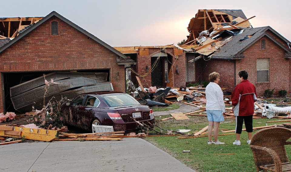 Photo - Neighbors stand in the front yard of one of the eight homes damaged or destroyed on Broadway in a neighborhood surrounding the Cedar Valley East Golf Course after a tornado came through the area Tuesday afternoon,  May 24, 2011,   Photo by Jim Beckel, The Oklahoman