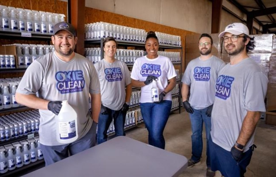 Photo -  Okie Clean co-founders Jonathan Jordan, Mason Haley, Raven Gonzaque, Nick Zenk and Sutton Clark, from left, pose for a photo with the Okie Clean Hand Sanitizer and all purpose cleaner product at the Okie Clean warehouse in Oklahoma City. [Chris Landsberger/The Oklahoman]
