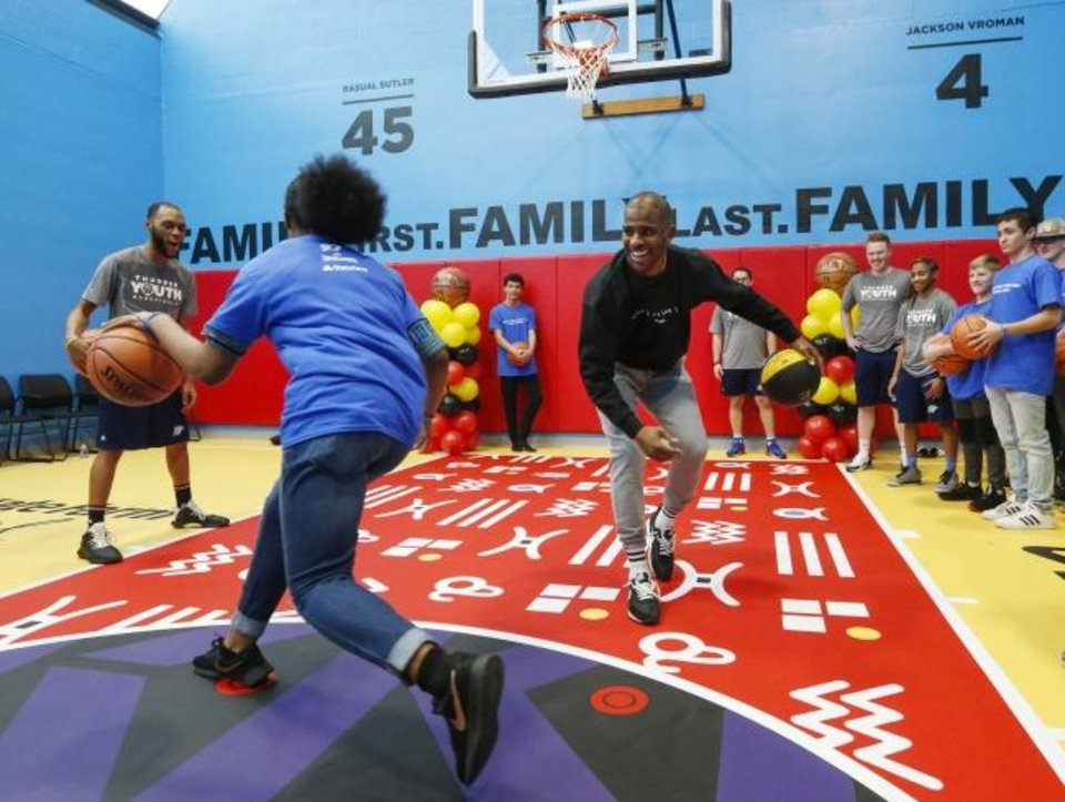 Photo -  Oklahoma City Thunder point guard Chris Paul leads a basketball clinic with youth from Family TREE in Oklahoma City after the dedication of a refurbished basketball court. The refurbishment was completed by a partnership of the Chris Paul Family Foundation, Spalding and State Farm. [Nate Billings/The Oklahoman]