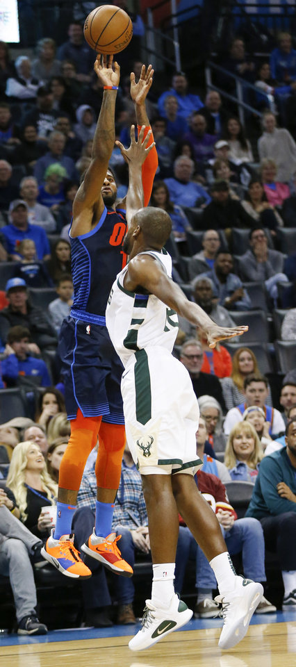 Photo - Oklahoma City's Paul George (13) takes a three-point shot over Milwaukee's Khris Middleton (22) in the fourth quarter during an NBA basketball game between the Milwaukee Bucks and the Oklahoma City Thunder at Chesapeake Energy Arena in Oklahoma City, Sunday, Jan. 27, 2019. Oklahoma City won 118-112. Photo by Nate Billings, The Oklahoman