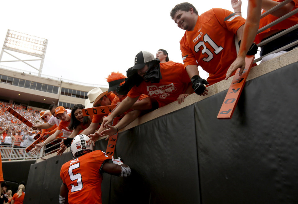 Photo - Oklahoma State's Justice Hill (5) celebrates with fans after scoring a touchdown in the second quarter during a college football game between the Oklahoma State Cowboys (OSU) and the Boise State Broncos at Boone Pickens Stadium in Stillwater, Okla., Saturday, Sept. 15, 2018. OSU won 44-21. Photo by Sarah Phipps, The Oklahoman