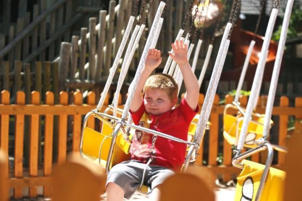 Photo -  Kalvin, 4, rides Bubba's Honey Swings on June 28 in the newly revamped Timber Town kids area of Frontier City in Oklahoma City. [Paxson Haws/The Oklahoman]