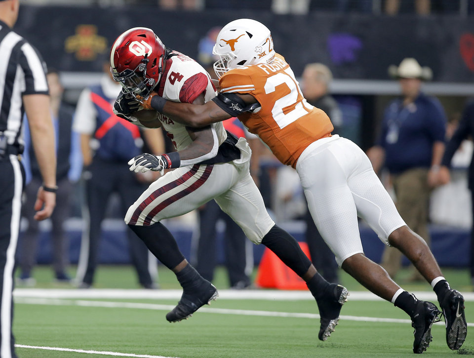 Photo - Oklahoma's Trey Sermon (4) scores a touchdown in front of B.J. Foster (25) of Texas during the Big 12 Championship football game between the Oklahoma Sooners (OU) and the Texas Longhorns (UT) at AT&T Stadium in Arlington, Texas, Saturday, Dec. 1, 2018.  Oklahoma won 39-27. Photo by Bryan Terry, The Oklahoman
