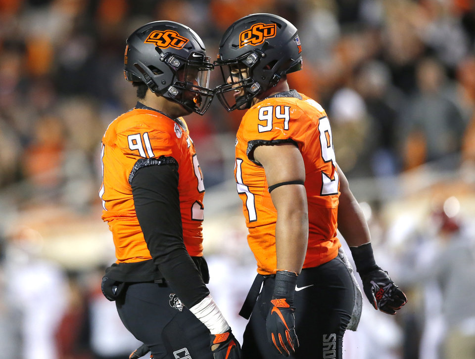 Photo - Oklahoma State's Trace Ford (94) and Mike Scott (91) celebrate a sack in the first quarter during the Bedlam college football game between the Oklahoma State Cowboys (OSU) and Oklahoma Sooners (OU) at Boone Pickens Stadium in Stillwater, Okla., Saturday, Nov. 30, 2019. OU won  34-16. [Sarah Phipps/The Oklahoman]