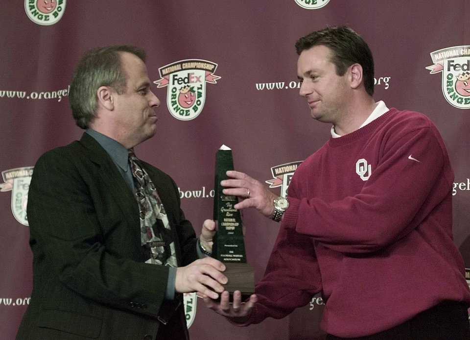 Photo - NATIONAL CHAMPIONSHIP, COLLEGE FOOTBALL: OU FSU ORANGE BOWL:  Dave Sittler presents the Sports Writers Coach of the Year award to OU head coach Bob Stoops at a press conference following the Sooners victory over Florida State in the Orange Bowl.  Staff Photo by Steve Sisney