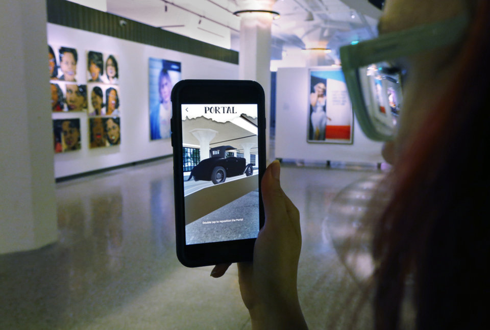 Photo -  Kenna Jackson, with Trifecta Communications, uses an augmented reality app on her mobile phone to view the 21c Museum Hotel building as it would have appeared in 1916. [Photo by Steve Sisney, The Oklahoman]