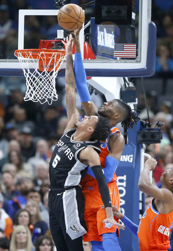 Photo - Oklahoma City's Nerlens Noel (9) blocks the shot of San Antonio's Dejounte Murray (5) during an NBA basketball game between the Oklahoma City Thunder and the San Antonio Spurs at Chesapeake Energy Arena in Oklahoma City, Sunday, Feb. 23, 2020. [Bryan Terry/The Oklahoman]