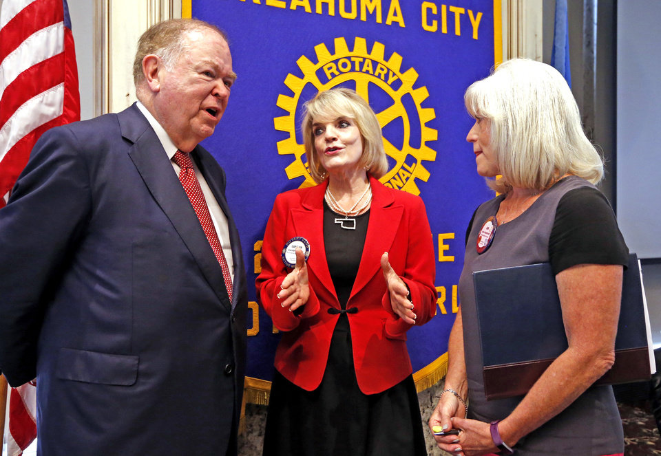 Photo -  University of Oklahoma President David Boren and Oklahoma Municipal League Executive Director Carolyn Stager, center, talk Tuesday after debating State Question 779 at the Rotary Club of Oklahoma City luncheon. At right is Chair of the Day Ann Ackerman. [Photo by Steve Sisney, The Oklahoman]