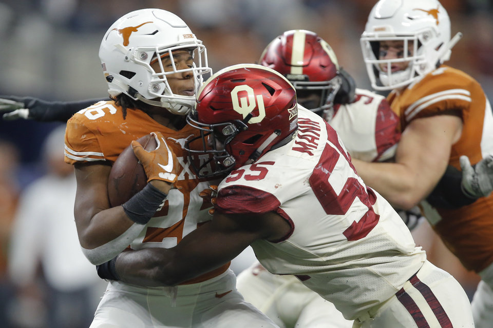 Photo - Oklahoma's Kenneth Mann (55) brings down Keaontay Ingram (26) of Texas during the Big 12 Championship football game between the Oklahoma Sooners (OU) and the Texas Longhorns (UT) at AT&T Stadium in Arlington, Texas, Saturday, Dec. 1, 2018.  Oklahoma won 39-27. Photo by Bryan Terry, The Oklahoman
