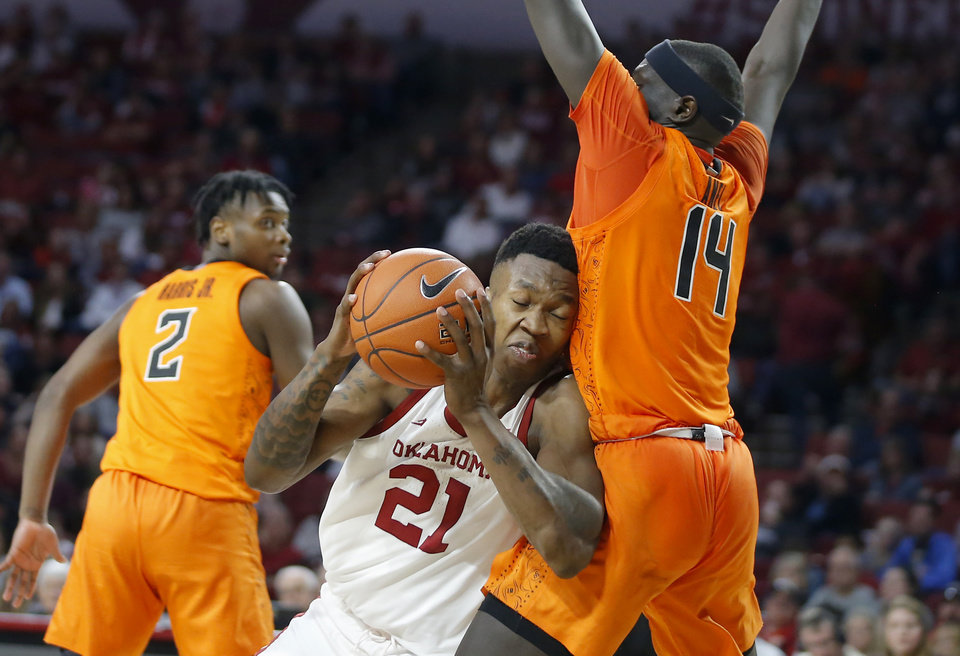 Photo - Oklahoma's Kristian Doolittle (21) tries to get past Oklahoma State's Yor Anei (14) during a Bedlam college basketball game between the University Oklahoma Sooners (OU) and the Oklahoma State Cowboys (OSU) at the Lloyd Noble Center in Norman, Okla., Saturday, Feb. 1, 2020. Oklahoma won 82-69. [Bryan Terry/The Oklahoman]