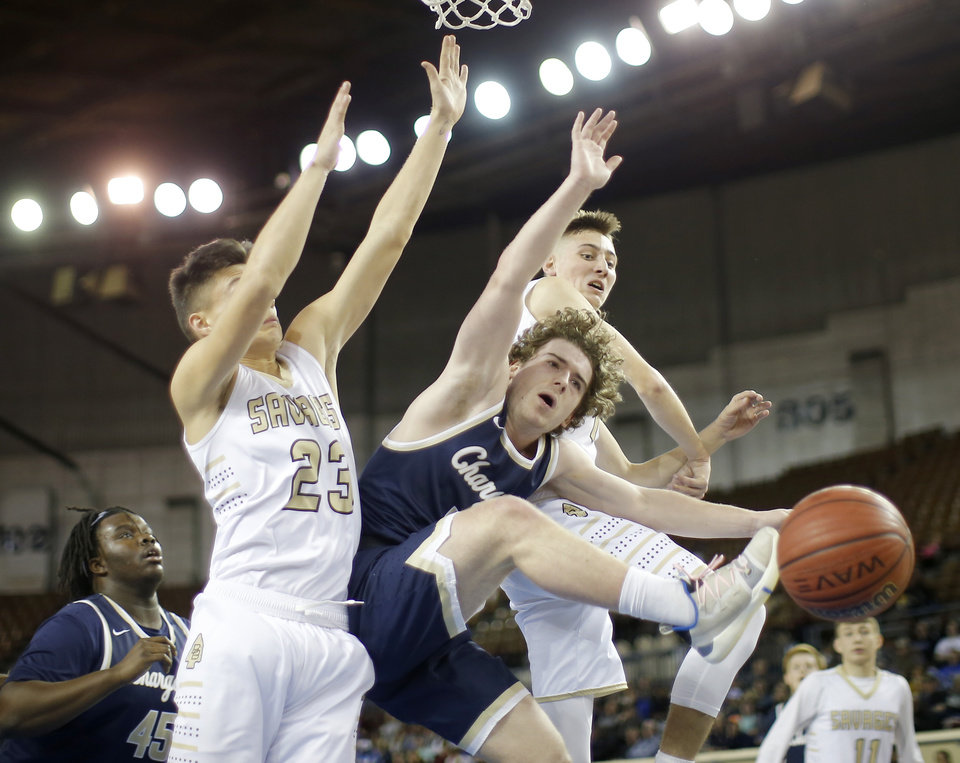 Photo - Heritage Hall's Jack Spainer is Kyle Park, left, and Jace Jordan as he goes to the basket defended by Broken Bow's during a Class 4A state tournament basketball game between Heritage Hall and Broken Bow High School in Jim Norick Arena at State Fair Park in Oklahoma City, Thursday, March 7, 2019. Photo by Bryan Terry, The Oklahoman