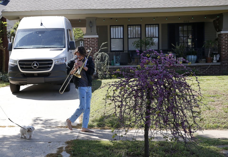 Photo - Christian Pearson plays a tune for a dog as he walks in the Gatewood neighborhood in Oklahoma City, Friday, April 10, 2020. [Sarah Phipps/The Oklahoman]