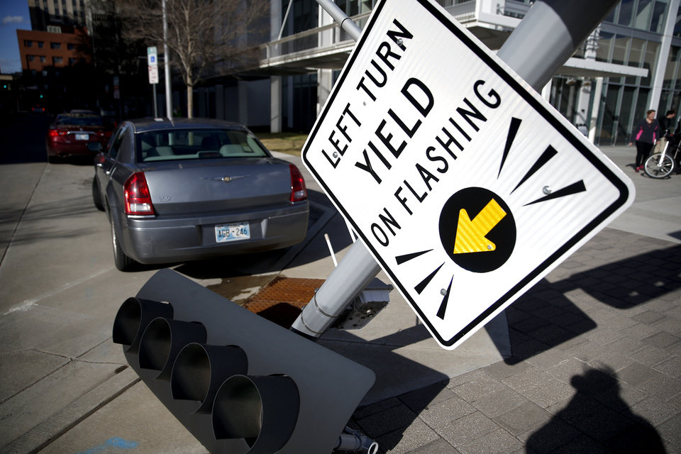 Photo - Pedestrians wait to cross W. Sheridan Avenue traffics signal is pictured on the ground after the wind knocked it over in downtown Oklahoma City,  Wednesday, March 13, 2019. Photo by Sarah Phipps, The Oklahoman