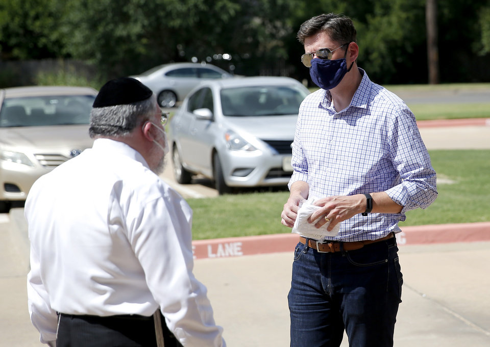 Photo - Rabbi Ovadia Goldman and Mayor David Holt talk during a free drive-thru mask distribution at the Chabad Community Center for Jewish Life & Learning in Oklahoma City, Wednesday, July 8, 2020. Photo by Sarah Phipps, The Oklahoman