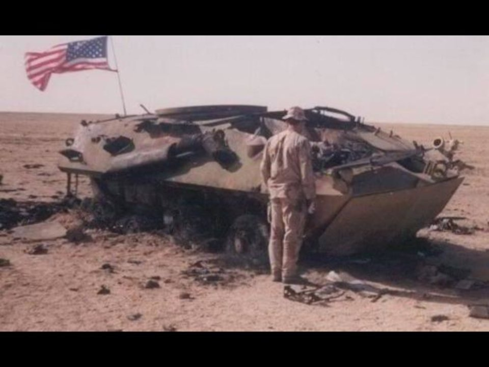 Photo -  Marine Cpl. Stephen Bentzlin and Marine Sgt. Garett Mongrella were among seven crew members of Red 2, a LAV-25 vehicle, who were killed in action in January 1991 during Operation Desert Storm. One crew member survived. A Marine is pictured showing his respects at the site where crew members lost their lives.