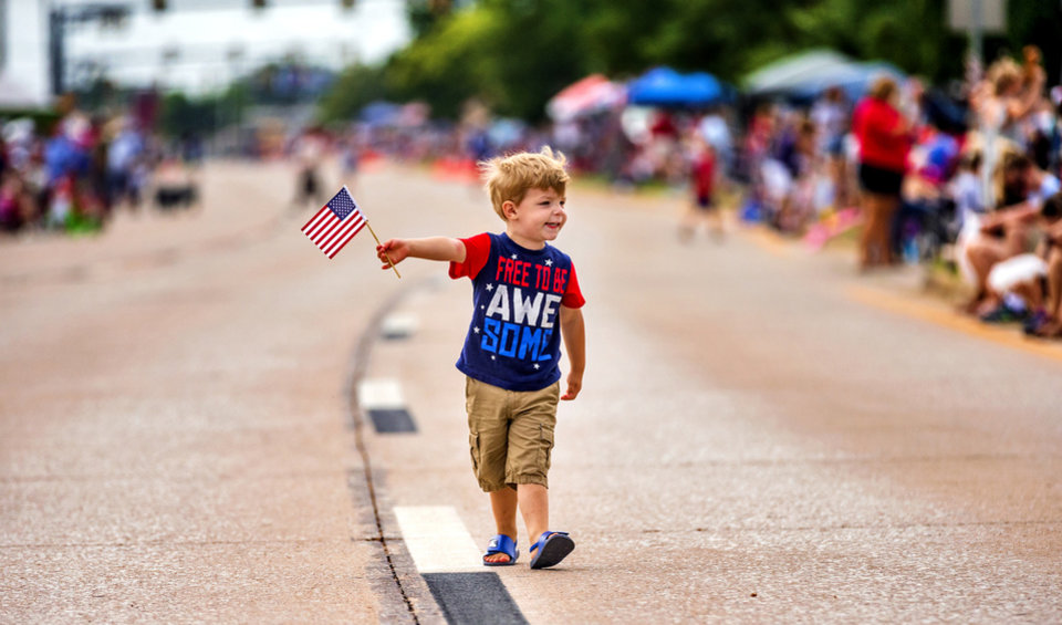 Photo - Finn Emerich, 3, walks down the street waving his American Flag to those lining the street for the start of the Bethany Freedom Festival parade in Bethany, Okla. on Thursday, July 4, 2019.    [Chris Landsberger/The Oklahoman]