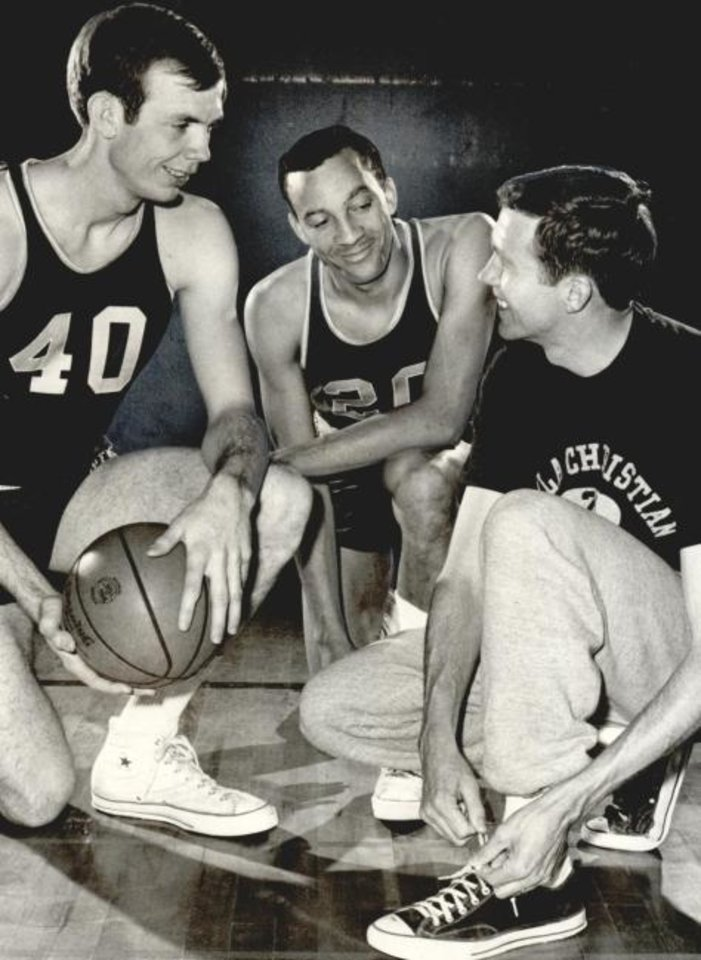 Photo -  Billy Brooks, center, is shown in this 1968 Oklahoma Times photo, with his fellow Oklahoma Christian College teammate David Smith (40) and the team's coach Frank Davis, at right.