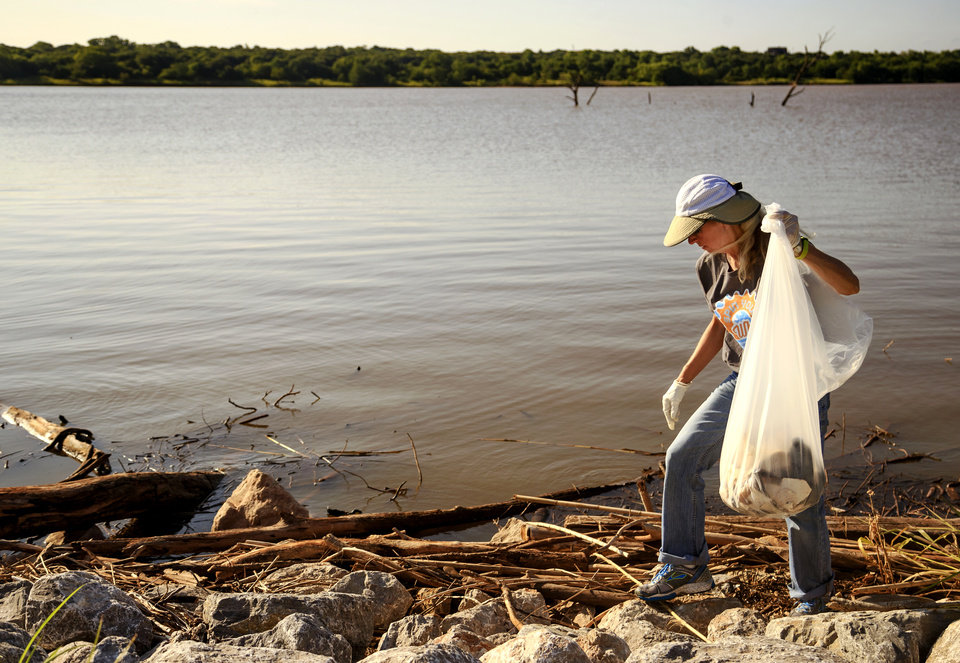 Photo -  Terry Cloud works to fill a bag Tuesday as she picks up trash at Lake Arcadia's Carl Reherman Park in Edmond. [Photo by Chris Landsberger, The Oklahoman]
