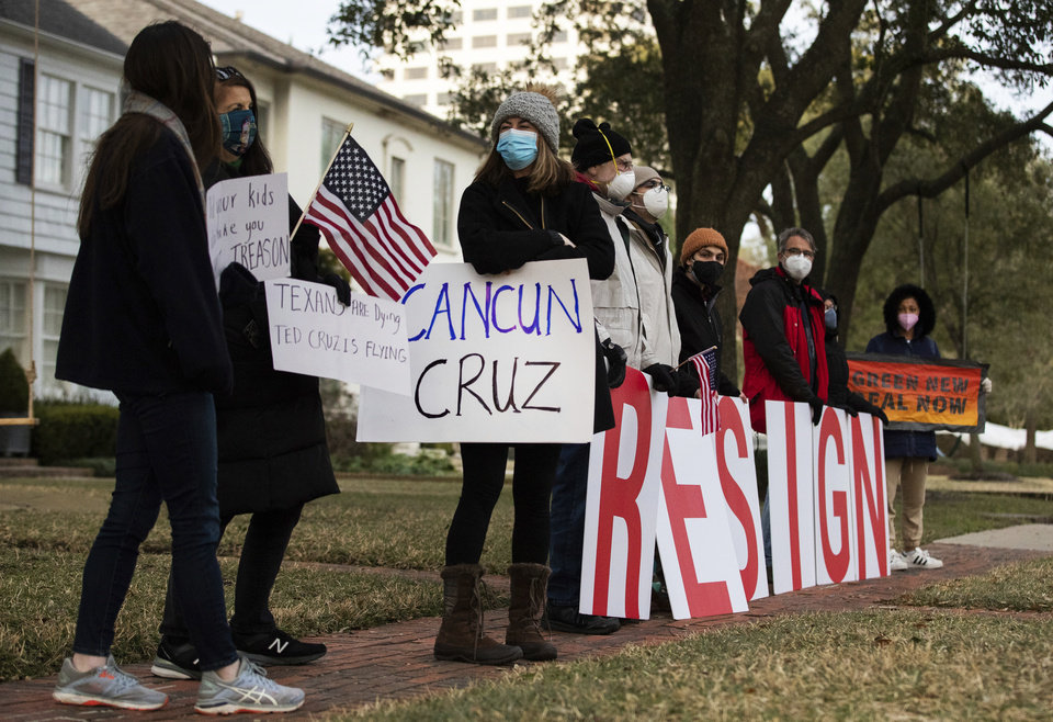 Photo -  FILE - In this Feb. 18, 2021, file photo, demonstrators stand in front of U.S. Sen. Ted Cruz's home demanding his resignation in Houston. Cruz has acknowledged that his family vacation to Mexico was