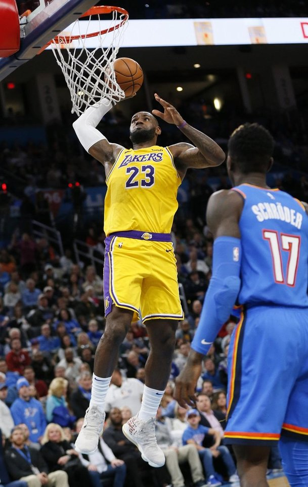 Photo - Los Angeles' LeBron James (23) dunks the ball in front of Oklahoma City's Dennis Schroder (17) in the third quarter during an NBA basketball game between the Oklahoma City Thunder and the Los Angeles Lakers at Chesapeake Energy Arena in Oklahoma City, Friday, Nov. 22, 2019. [The Oklahoman Archives]