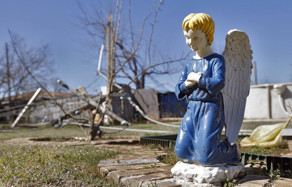 Photo - A angel statue still stands among storm debris to a home in Moore, Okla. on Thursday, March 26, 2015. A tornado hit the area on Wednesday evening causing damage in the area.  Photo by Chris Landsberger, The Oklahoman