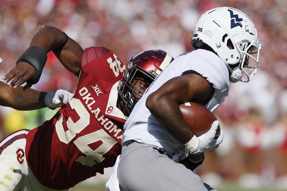 Photo - Oklahoma's David Ugwoegbu (34) chases down West Virginia's T.J. Simmons (1) during a college football game between the University of Oklahoma Sooners (OU) and the West Virginia Mountaineers at Gaylord Family-Oklahoma Memorial Stadium in Norman, Okla, Saturday, Oct. 19, 2019. Oklahoma won 52-14. [Bryan Terry/The Oklahoman]