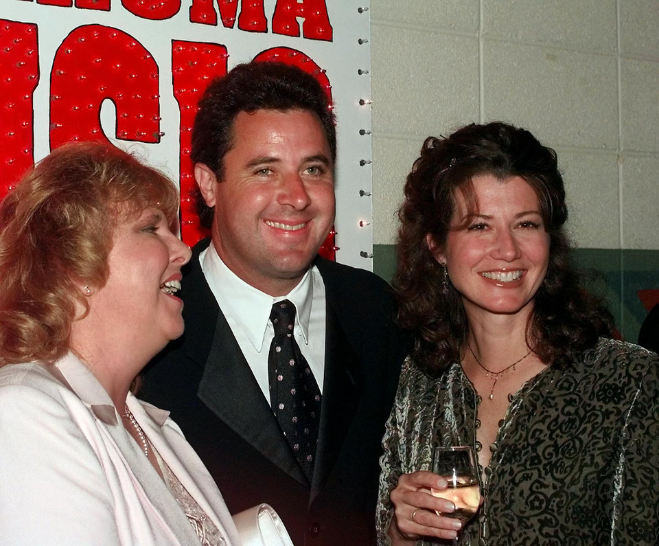 5ebcfb8643f522 Vince Gill and girlfriend Amy Grant pose for pictures with an unidentified  fan at a private