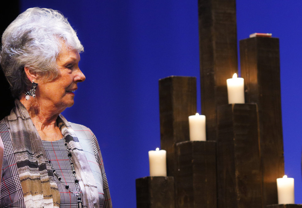 "Photo - Helga Page, who survived the Holocaust, poses with a group by the candles after the ""Testimony of a Child, the Holocaust Remembrance Day program at Bishop McGuinness High School auditorium, Sunday, May 5, 2019. [Doug Hoke/The Oklahoman]"